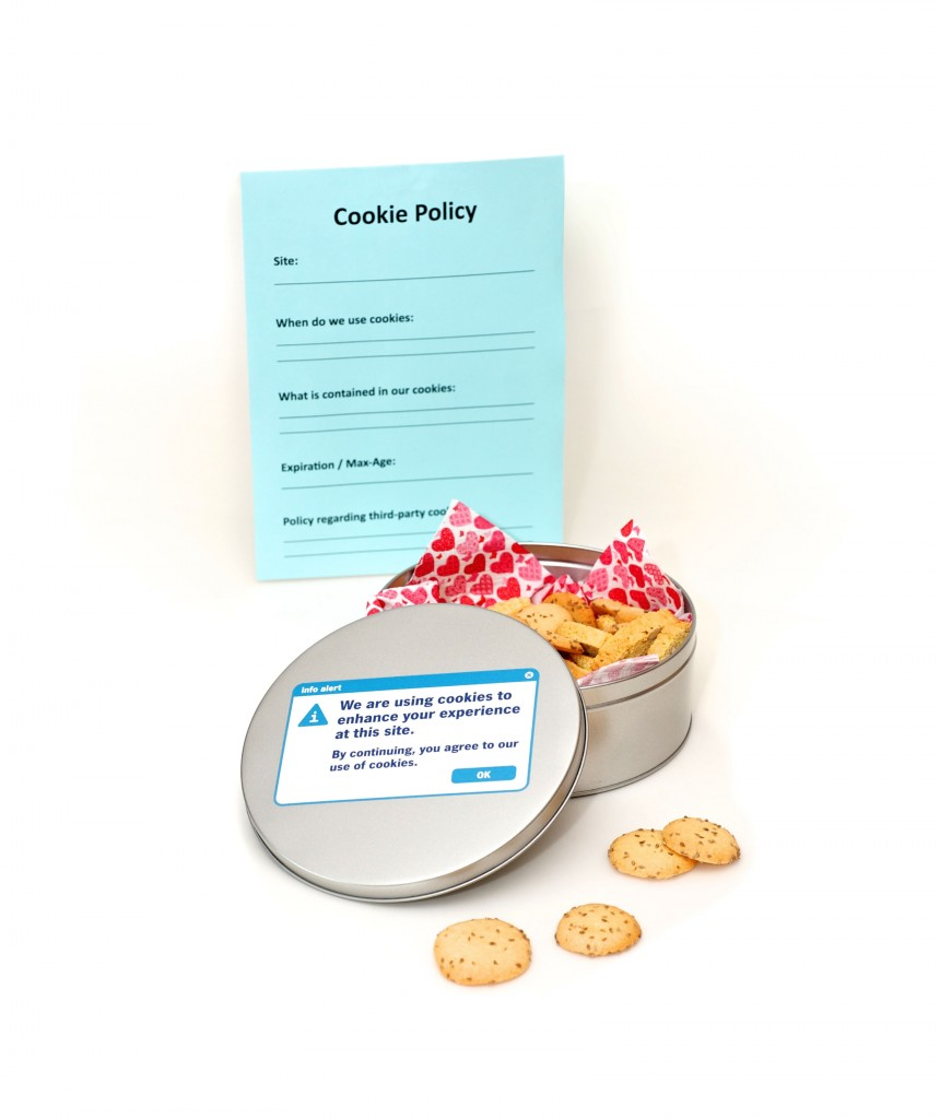 A metal cookie tin with some cookies in it. On the lid is printed: We are using cookies to enhance your experience at this site. By continuing, you agree to our use of cookies.