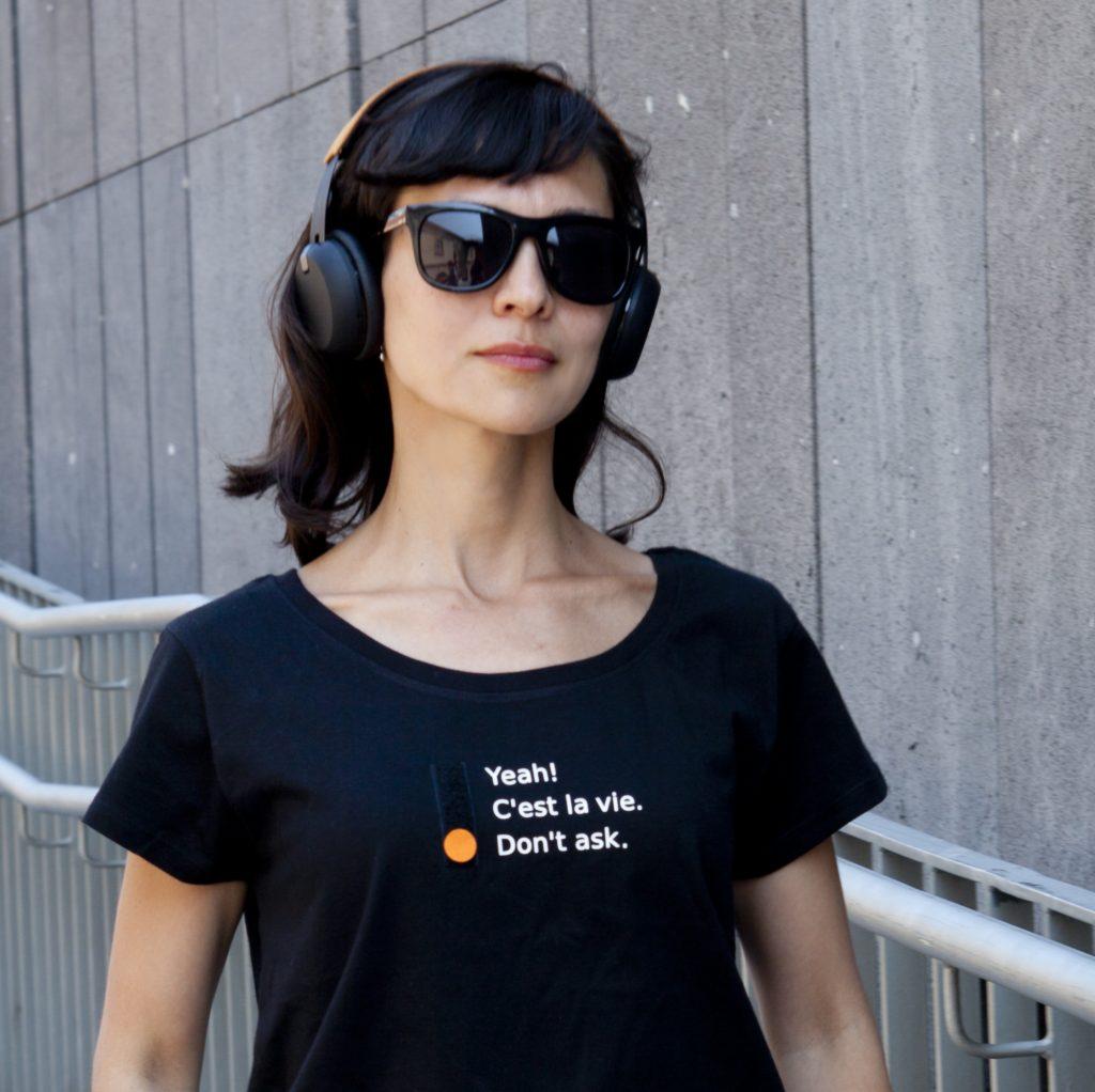 Dame mit Kopfhörer, ernstes Gesicht. Auf ihrem Shirt (Aufschrift Yeah / Cest la vie / Dont ask) ist die Option Dont ask gesetzt.